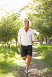 Middle Aged Man Jogging In Park. Smiling At Camera Royalty Free Stock Photography