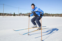 Middle-aged man jumping in the air with skis Stock Images