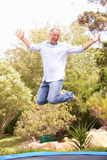 Middle Aged Man Jumping On Trampoline In Garden. With arms up royalty free stock photo