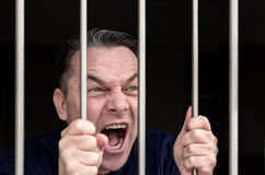 Middle-aged man kept captive in a prison cell Royalty Free Stock Photos