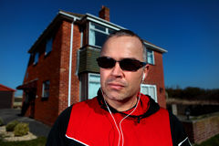 Middle Aged Man Listening to Music. Sporty man wearing earphones and sunglasses in front of house on sunny day Royalty Free Stock Photography