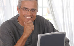 Middle Aged Man in Living room with computer Royalty Free Stock Photography