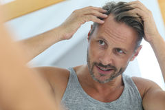 Middle-aged man looking himself in the mirror. Middle-aged man concerned by hair loss royalty free stock photo