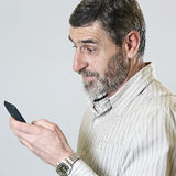 Middle aged man looking at his phone Royalty Free Stock Photos