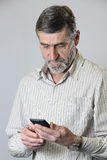Middle aged man looking at his phone Royalty Free Stock Photography