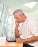 Middle aged Man Looking Intently at Laptop Stock Photos