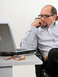 Middle aged man looking at laptop Stock Images