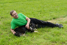 Middle aged man. Lying on the grass with a dog Royalty Free Stock Photo