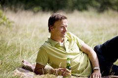 A middle aged man lying on the grass, having a beer Stock Images