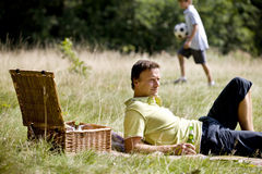 A middle aged man lying on the grass, having a beer Royalty Free Stock Photography