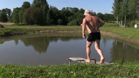 Middle-aged man make head jump into pond water from bridge stock video