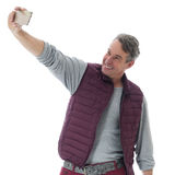 Middle-aged man makes a self portrait. He is wearing a red vest. stock image