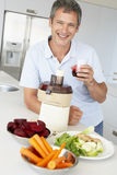 Middle Aged Man Making Fresh Vegetable Juice Stock Photography
