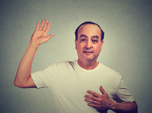 Middle aged man making a promise. On gray wall background Royalty Free Stock Image