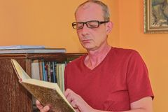Middle aged man man is reading book in living room. Mature man is standing next to bookcase royalty free stock photos