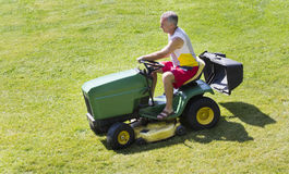 Middle-Aged Man Mowing lawn on riding mower Stock Images
