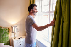 Middle aged man opens curtains in hotel room in the morning Royalty Free Stock Image