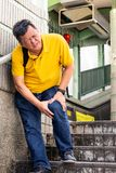 Man with painful knee struggle walking down flight of stairs royalty free stock photo