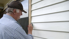Middle-aged Man Painting Weatherboards. Royalty Free Stock Photography