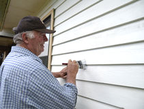 Middle-aged Man Painting Weatherboards. Stock Photography