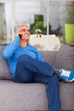 Middle aged man phone. Happy middle aged man talking on cell phone at home Royalty Free Stock Photos