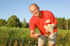 Middle-aged man picking up flowers Royalty Free Stock Images