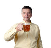Middle aged man with pint of beer. Senior male holding a pint of brown ale in english style mug and raising the drink in a greeting stock photos