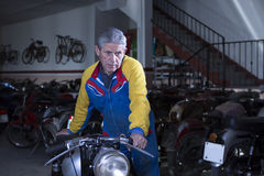 Middle aged man placing a motorbike Royalty Free Stock Photography
