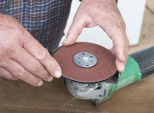 Middle-aged Man Placing Sanding Disk onto Holder. Stock Photography