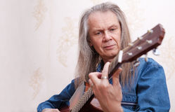 Middle-aged man playing guitar closeup Stock Photo