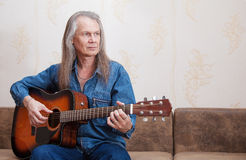 Middle-aged man playing guitar Stock Photography