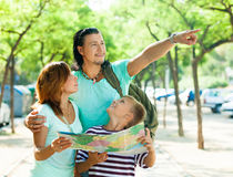 Middle-aged man pointing the direction for family. Middle-aged men pointing the direction for wife and son at city Stock Photos