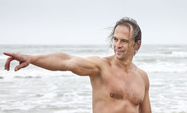 Middle-aged man  points to the something in the sea Stock Image