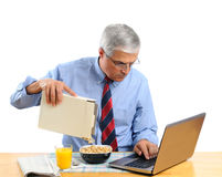 Middle Aged Man Pouring Cereal into a Bowl. Middle aged man pouring his breakfast cereal into bowl. He is is busy working on his laptop computer and not paying Royalty Free Stock Photography