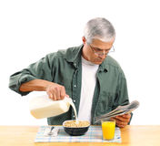 Middle Aged Man Pouring Milk into His Cereal Bowl. Casually dressed middle aged man pouring milk into his breakfast cereal bowl while reading the morning Stock Images