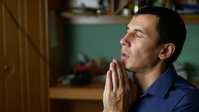 Middle-aged man praying god a indoor religion stock video