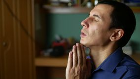Middle-aged man praying a indoor god religion stock footage