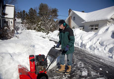 Middle-aged man pushing snow blower. Middle-aged man pushing a snow blower to clear snow from a suburban driveway after a storm.  Man is wearing noise protection Royalty Free Stock Images