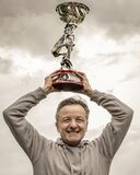 A middle-aged man raises a cup to the sky during an awards ceremony, with an expression of happiness, against a dramatic sky