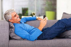 Middle aged man reading message. Middle aged man reading text message on mobile phone while lying on couch Royalty Free Stock Photo
