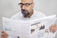 Middle aged man reading newspaper Stock Images