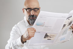 Middle aged man reading newspaper Stock Photography