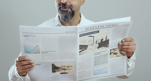 Middle aged man reading newspaper Royalty Free Stock Photos