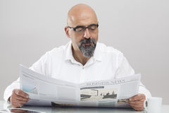 Middle aged man reading newspaper Stock Photo