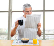 Middle Aged Man reading newspaper with breakfast Stock Photos