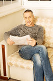 Middle-aged man reading newspaper at home Royalty Free Stock Image