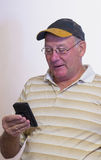 Middle-aged Man Reading Text Message. A middle-aged man looks at the screen on his mobile phone as he reads a text message Stock Image