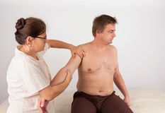 Middle aged man receives bowen massage treatment for his arm Stock Image