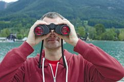 A man with binoculars  at the lake. A middle-aged man in  a red sweater with a binoculars observing nature at the lake on a cloudy day Stock Images