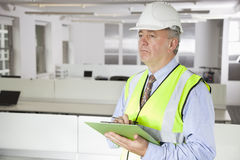 Middle-aged man in reflector vest and hard hat with clipboard at office Royalty Free Stock Images
